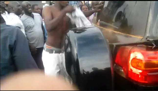 For the love: Crazy supporter removes his shirt in order to clean the car of a popular NASA governor