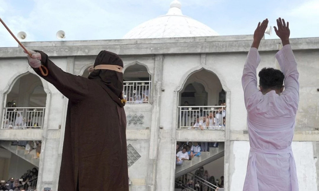 Man and woman publicly caned until they collapse for being intimate outside of marriage (photos)