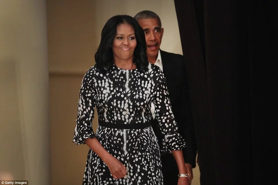 Obama and Michelle (pictured earlier in Chicago) arrived at the luxury village aboard a private jet