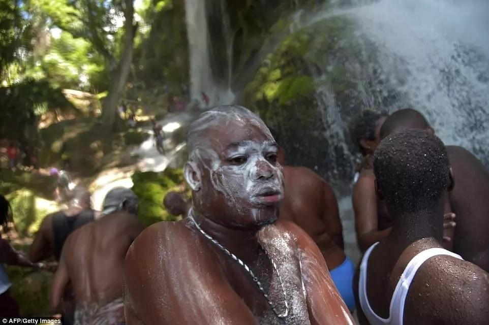 """Voodoo believers seen bathing in the """"healing"""" waterfall. Photo: AFP/Getty Images"""
