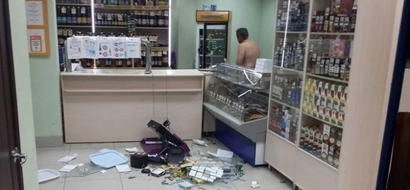 Watch hilarious footage of a naked madman going nuts in shop!
