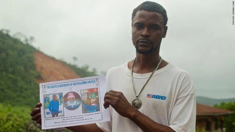 Gabriel Fattah Manga displays photos of the family members he lost. Photo: CNN