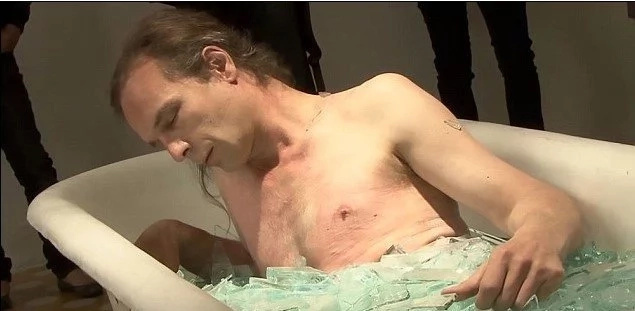Crazy! Artist spends 60 minutes in bath full of GLASS with his clothes off (photos)