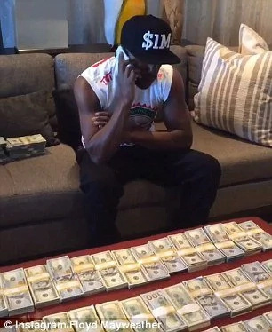 Floyd Mayweather poses with cash as he boasts of his fortunes